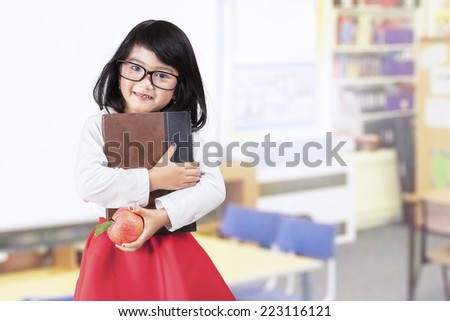 Attractive little asian girl holding a book and apple in classroom - stock photo