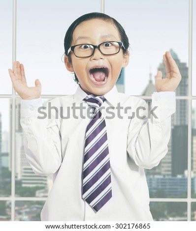 Attractive little boy wearing a tie in the office and looks shocked - stock photo
