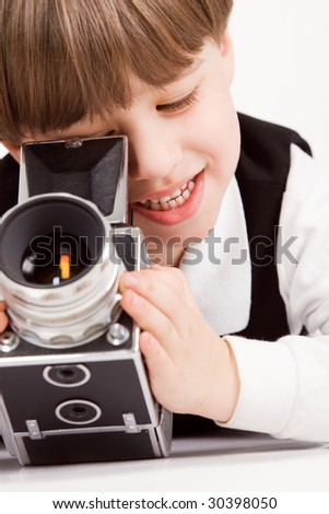 Attractive little boy with photo camera over white