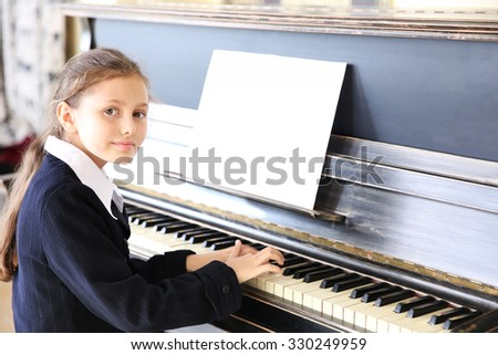 Attractive little girl plays piano - stock photo