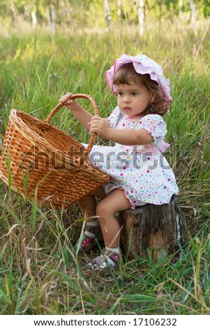 Attractive little girl sitting on a stub and holding a basket