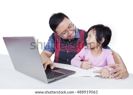 Attractive little girl talking and studying with her father while using a book and laptop, isolated on white background