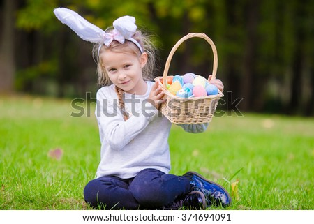 Attractive little girl wearing bunny ears with a basket full of Easter eggs on spring day outdoors - stock photo