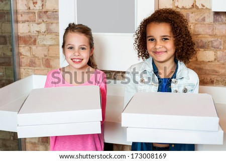 Attractive little girls posing with pizza boxes - stock photo