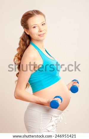 Attractive long hair pregnant caucasian woman do fitness against white background, sporty lifestyle, health care, happy and healthy pregnancy concept - stock photo