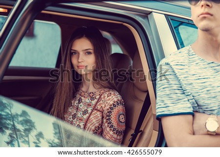 Attractive long hair woman in a car and a guy. - stock photo