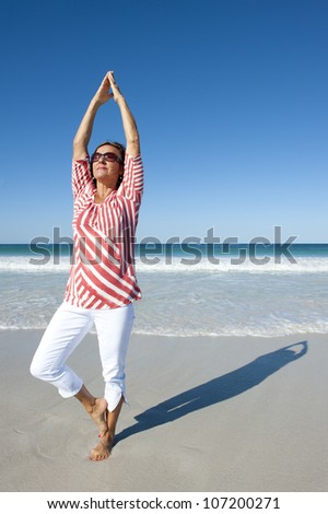 Attractive looking mature woman, happy doing exercises at beach, isolated with ocean and blue sky as background and copy space. - stock photo