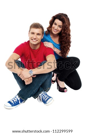 Attractive love couple sitting relaxed on floor. Indoor studio shot - stock photo