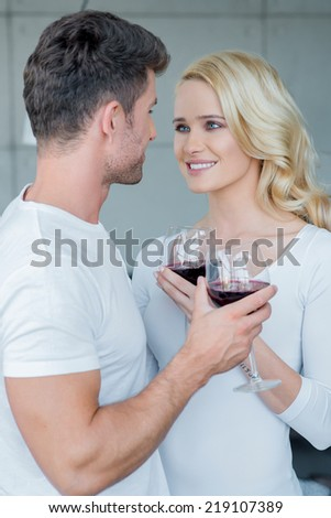 Attractive loving couple enjoying a romantic glass of red wine standing smiling into each others eyes with focus to the pretty blond wife - stock photo
