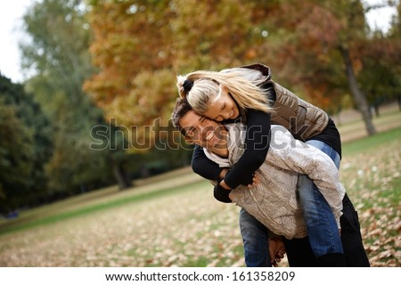 Attractive loving couple having fun in autumn park, laughing, piggyback. - stock photo