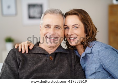 Attractive loving middle-aged couple posing arm in arm on a sofa at home smiling happily at the camera, head and shoulders view - stock photo