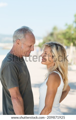 Attractive loving middle-aged couple standing looking into each others eyes as they relax at the beach on a hot summer day - stock photo
