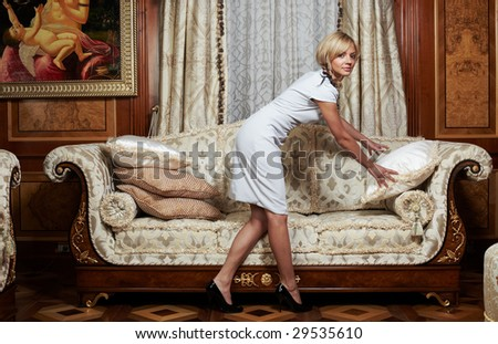 Attractive maid making a sofa in luxury hotel - stock photo