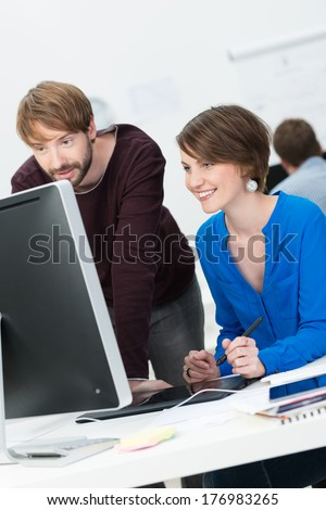 Attractive male and female co-workers working in cooperation at the office - stock photo