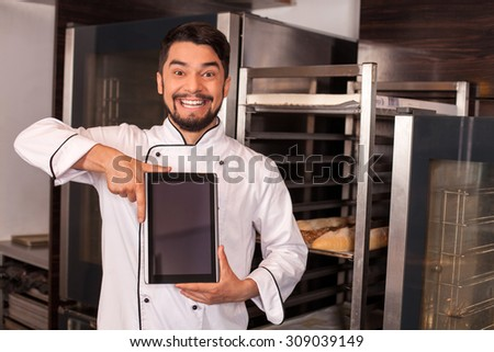 Attractive male baker is holding a tablet and presenting the screen with joy. The man is standing in bakery and smiling. Copy space in right side - stock photo