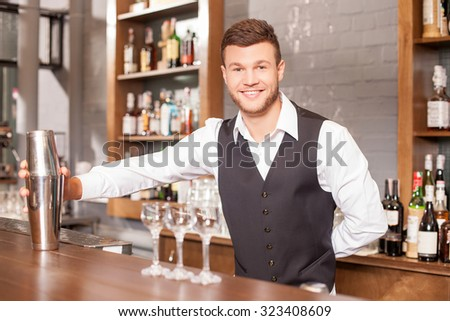 Attractive male bartender is holding a shaker and mixing drink. He is standing at counter near glasses. The man is looking forward and smiling - stock photo