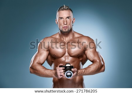 Attractive male body builder as photograph holding a camera on blue background