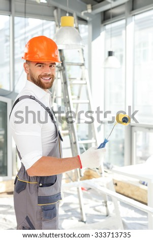 Attractive male builder is ready to paint the walls. He is standing and holding a roller. The man is looking at camera and smiling - stock photo