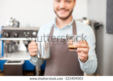 Attractive male cafe worker is showing a glass of espresso. He is standing and smiling. The man is looking forward happily. Focus on cup - stock photo
