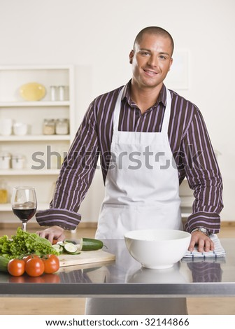 Attractive male chef in the kitchen with vegetables and a glass of wine on the counter. Vertical - stock photo