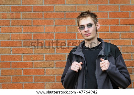 Attractive Male college student in front of an exterior of a brick wall school. - stock photo