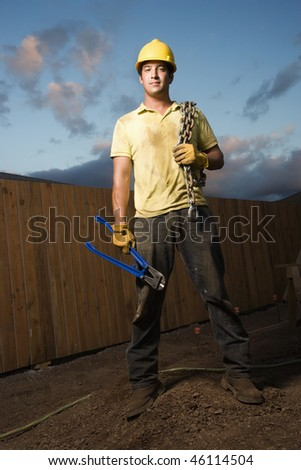 Attractive male construction worker in a hardhat stands at a construction site with bolt cutters and a chain. Vertical shot. - stock photo