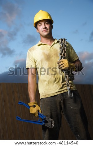 Attractive male construction worker in a yellow hardhat smiles into the camera. He holds a heavy chain on his shoulder and bolt cutters in his hand. Vertical shot. - stock photo