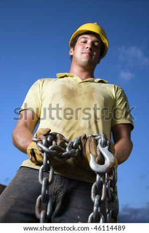 Attractive male construction worker wearing a yellow hardhat and work gloves looks down at the camera while holding a heavy chain and hook. Vertical shot - stock photo