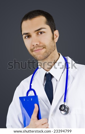 Attractive male doctor holding a clipboard - stock photo