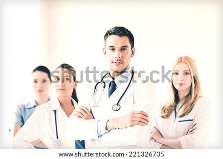 attractive male doctor in front of medical group - stock photo