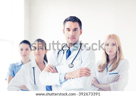 attractive male doctor in front of medical group