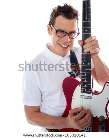 Attractive male guitarist playing guitar against white background - stock photo