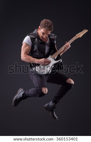 Attractive male guitarist with a cool musical instrument - stock photo
