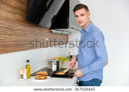 Attractive male in blue shirt standing and making pancakes on the kitchen