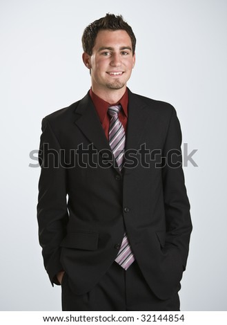 Attractive male looking at the camera, smiling. 3/4 body shot frontal view. Vertical