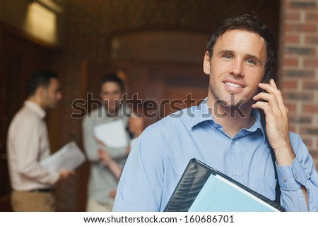 Attractive male mature student phoning with his smartphone on the corridor - stock photo
