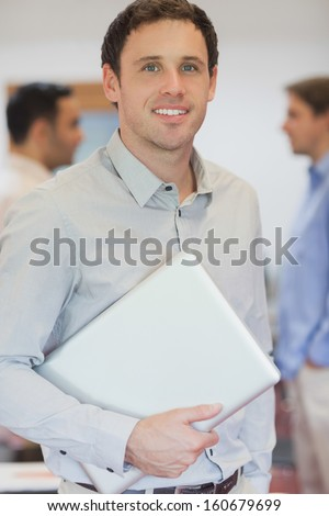 Attractive male mature student posing in classroom holding his laptop - stock photo