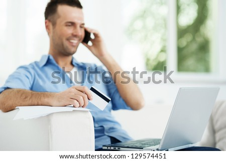 Attractive male paying bills - stock photo