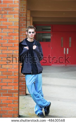 Attractive Male student in front of an exterior of a brick wall school. - stock photo