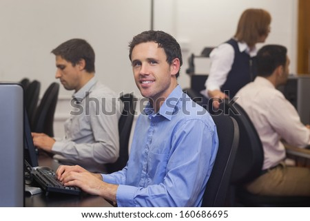 Attractive male student sitting in computer class smiling at camera - stock photo
