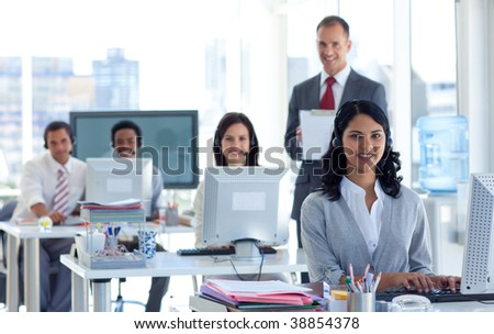 Attractive male supervisor writing notes in a call center - stock photo