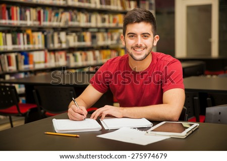 Attractive male university student doing some homework in the school library and smiling - stock photo