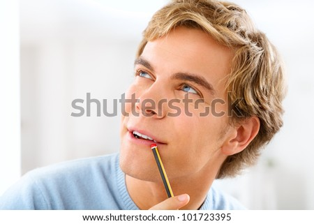 Attractive male university student holing pencil planning ahead - stock photo