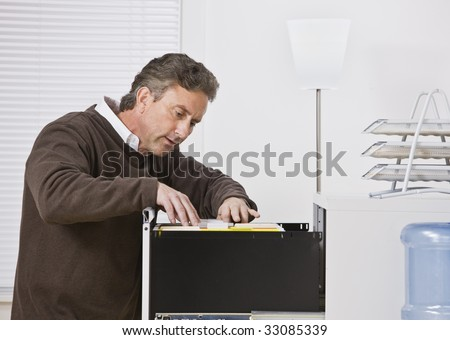 Attractive male wearing a sweater in office, looking for file in filing cabinet. Looking away from camera. Horizontal.