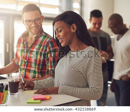 Attractive male wearing eyeglasses and flannel shirt standing next to female co-worker writing on sticky notes at desk with others behind them - stock photo