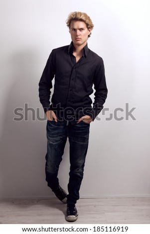 Attractive male with blonde hair, dressed in black shirt, blue jeans and gumshoes, with hands in his pockets, standing and looking at camera - stock photo