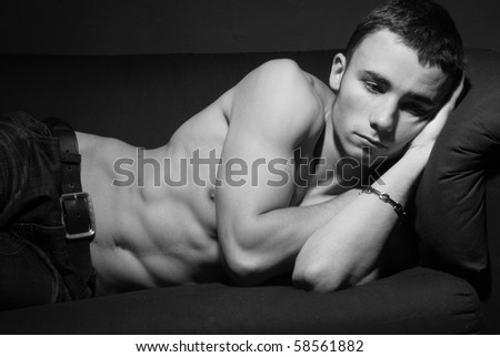Attractive male young man on the sofa - stock photo