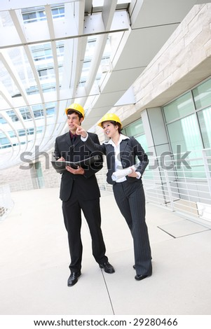 Attractive man and woman architects on building construction site - stock photo