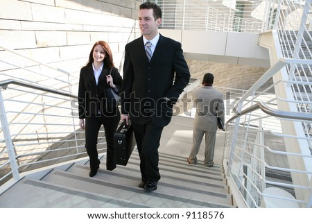 Attractive man and woman business people walking up the stairs - stock photo