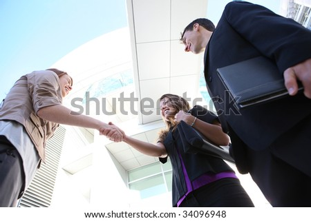Attractive man and woman business team shaking hands - stock photo